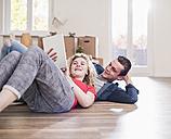 Happy young couple in new home lying on floor with tablet - UUF10740
