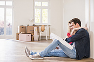 Young couple in new home sitting on floor looking at ground plan - UUF10743