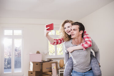 Happy young couple in new home taking a selfie - UUF10749