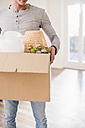 Young man carrying cardboard box in new home - UUF10752