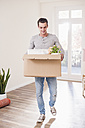 Young man carrying cardboard box in new home - UUF10755