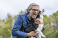 Portrait of happy senior man cuddling his dog - TCF05414