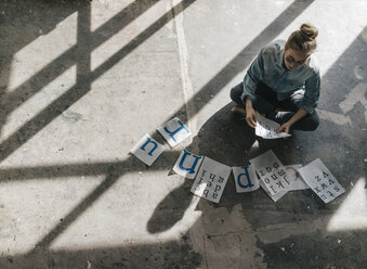 Young woman sitting on concrete floor working on letter templates - KNSF01472
