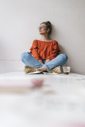 Young woman sitting on table thinking - KNSF01499