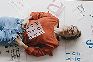 Young woman lying on table surounded by letter templates - KNSF01502