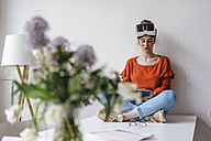 Young woman sitting on table using tablet wearing VR glasses - KNSF01514