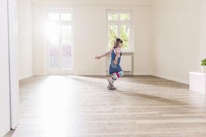 Happy girl running in empty apartment - UUF10760