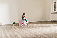 Girl in empty apartment holding teddy - UUF10763