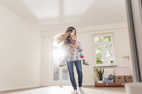 Happy mother and daughter in empty apartment - UUF10769