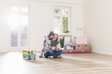Happy girl and mother with tablet in empty apartment - UUF10772