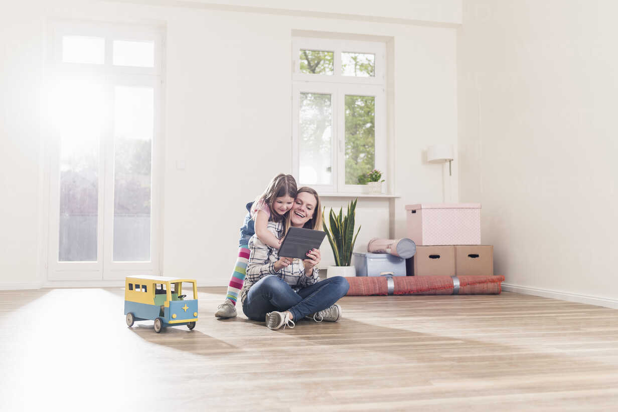 Happy girl and mother with tablet in empty apartment - UUF10772 - Uwe Umstätter/Westend61