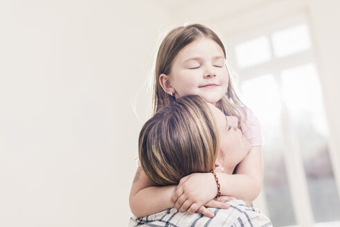 Mother and daughter hugging in empty apartment - UUF10775