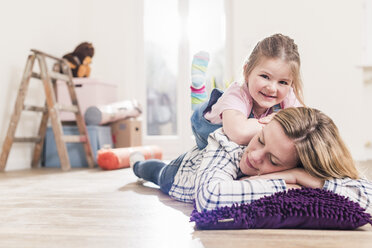 Mother and daughter having a break in new home - UUF10778