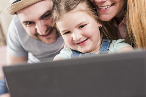 Smiling parents and daughter using tablet - UUF10784