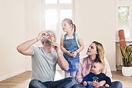 Family blowing soap bubbles in new home - UUF10787