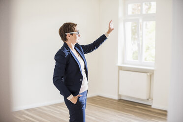 Woman in empty apartment wearing smartglasses - UUF10799