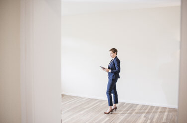 Woman in empty apartment with tablet - UUF10802