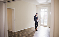 Woman in empty apartment looking at plan - UUF10805