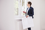 Woman in new apartment with plan and cell phone looking out of window - UUF10808