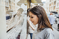 Young woman looking fascinated in shop window, boyfriend trying to pull her away - AIF00431
