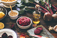 Bowl of Beetroot Hummus and ingredients on wood - RTBF00884