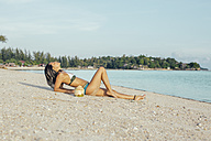 Woman relaxing on the beach - MOMF00169