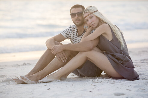 Young couple sitting on the beach, embracing - ZOCF00423