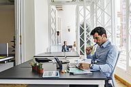 Businessman working in office, reading papers - JRFF01362