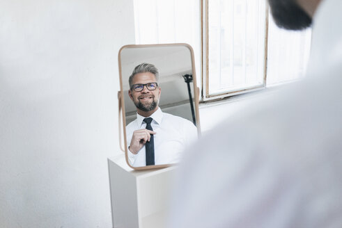 Businessman looking into mirror, fastening his tie - JOSF01017