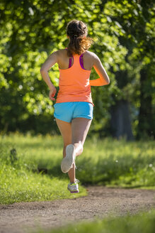 Young woman running in park - STSF01222