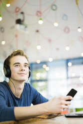 Portrait of relaxed young man listening music with headphones and smartphone in a coffee shop - JOSF01042