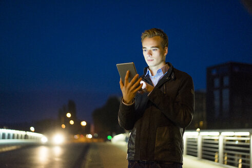 Young man using tablet qutdoors at night - JOSF01048
