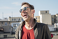 Portrait of laughing mature man with stubble wearing sunglasses - FMKF04151
