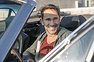 Portrait of smiling mature man sitting in his sports car - FMKF04160