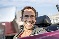 Portrait of smiling mature man sitting in his sports car - FMKF04163