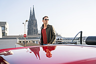 Germany, Cologne, portrait of mature man leaning with his parked sports car - FMKF04166