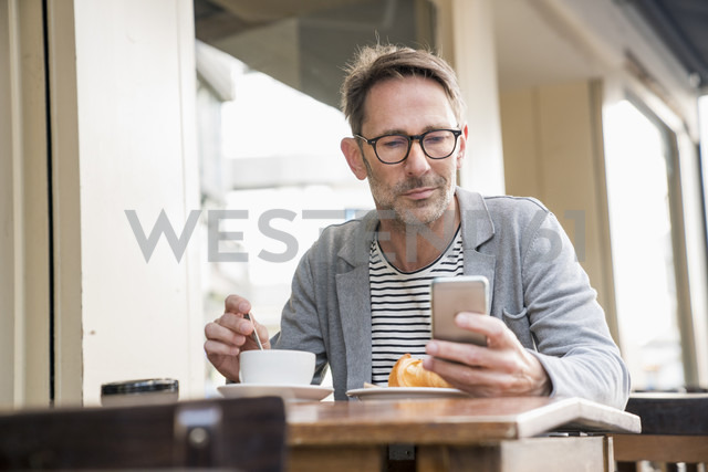 Portrait of mature man sitting at sidewalk cafe looking at cell phone - FMKF04169 - Jo Kirchherr/Westend61