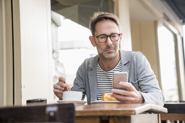 Portrait of mature man sitting at sidewalk cafe looking at cell phone - FMKF04169