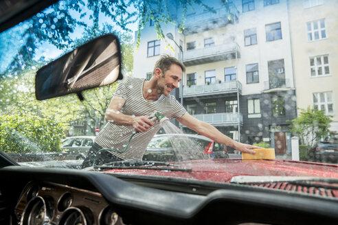 Smiling mature man washing his car - FMKF04172