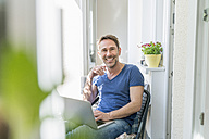 Portrait of smiling mature man sitting on balcony with laptop - FMKF04175