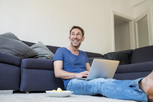 Portrait of laughing man with laptop sitting on the floor in the living room - FMKF04178