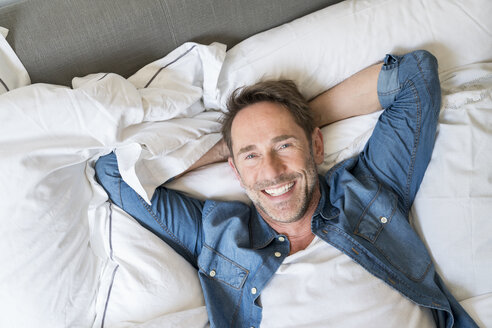 Portrait of happy mature man lying on  bed with hands behind head - FMKF04184