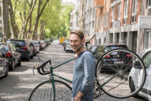 Portrait of smiling mature man carrying his bicycle on the shoulder - FMKF04187