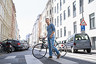 Portrait of smiling mature man with bicycle crossing the street - FMKF04193