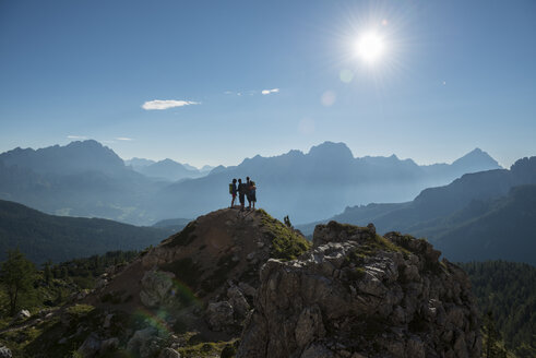 Italy, Friends standing om mountain top in the Dolomites, looking at view - ZOCF00465