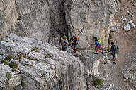 Italy, Friends climbing rocks in the Dolomites - ZOCF00474
