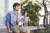 Man sitting on terrace with cup of coffee and woman in background - WESTF23168