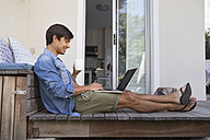 Man sitting on terrace using laptop - WESTF23171