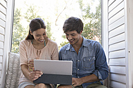 Smiling young couple sitting on windowsill sharing tablet - WESTF23195