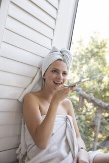 Laughing young woman wrapped in a towel holding cell phone - WESTF23201